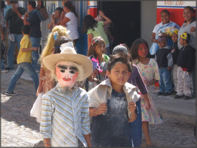 Children in the mardi gras parade with masks and drenched in flour.