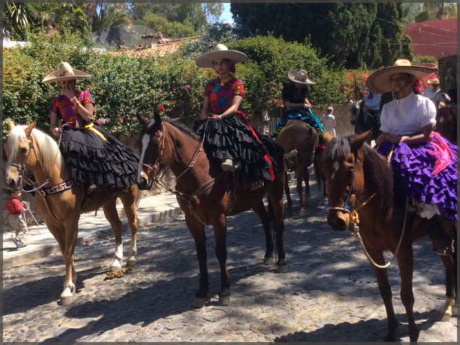Charras with ruffled skirts and sombreros on horses in the Carnival parade.