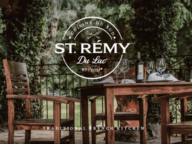 One of the few French Ajijic restaurants, St Remy,  with brown wooden chairs and fully set table set with wine.