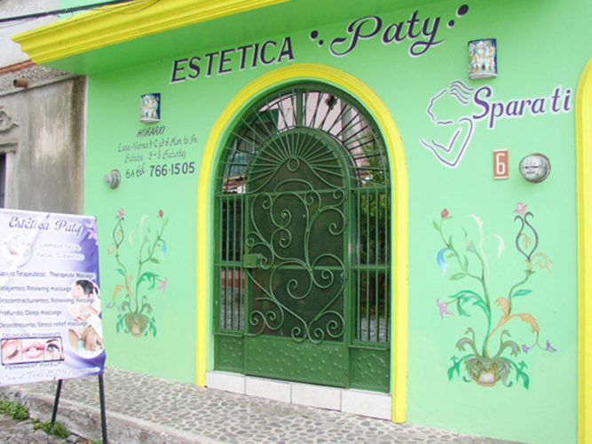 streetview of estetica paty with green walls colourful painted scrolls contact information sandwich board with offers out front