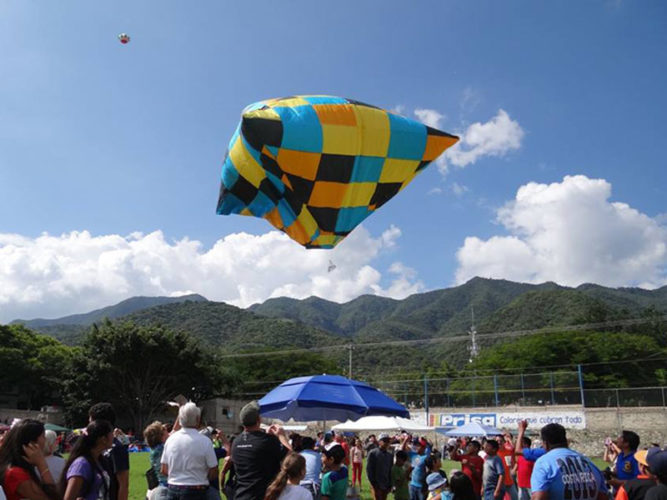 Colourful tissue paper globo floating in the air above field of spectators.