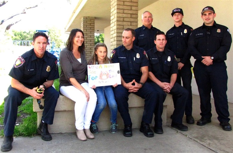 Surrounded by admiring firefighters, Christine Schick and her teacher Katherine Curt displayed the winning Woodsy Owl poster that Christine created for the Smokey Bear and Woodsy Owl Poster. he firefighters who came to congratulate Christine are (l to r) Brian Crain, Ben Thompson, Robert Westler, (and standing) Darrin Ward, Austin Delaney and Marouf Suleiman.