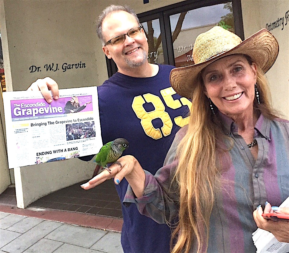 Chris Winkler and his 10-year-old parakeet, Chloe, with Shera Sandwell, and a copy of the street fair's only newspaper last year.