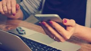 EscriboXti - mujer frente a su portatil mirando el movil
