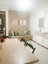 Sala com mesa de 4 lugares e sofá virado para a TV a cabo.