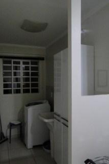 Área de serviço com tanquinho, maquina de lavar e armário.