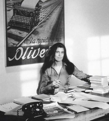 Susan Sontag, en su escritorio, con un cartel de Olivetti