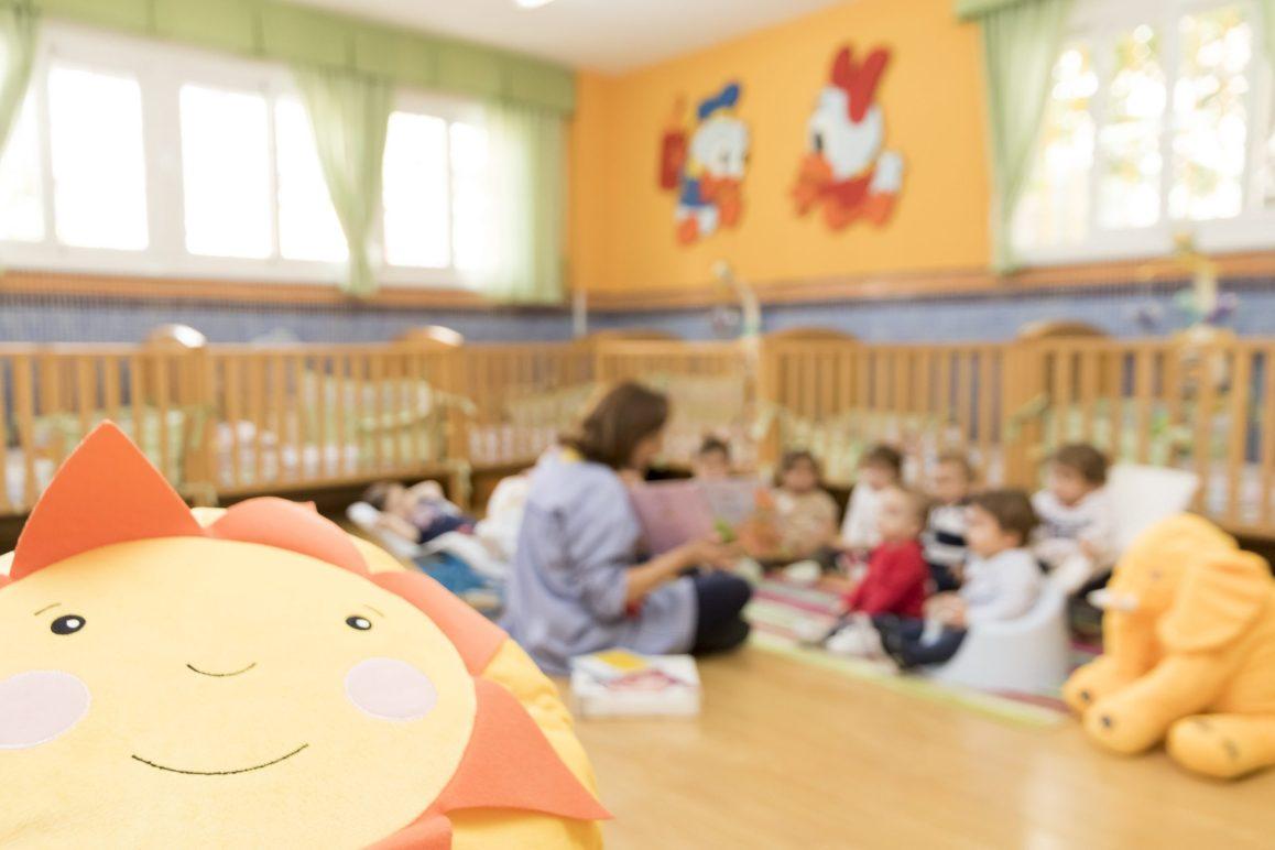 Educadora leyendo un cuento a los bebés de la Escuela Infantil Booma