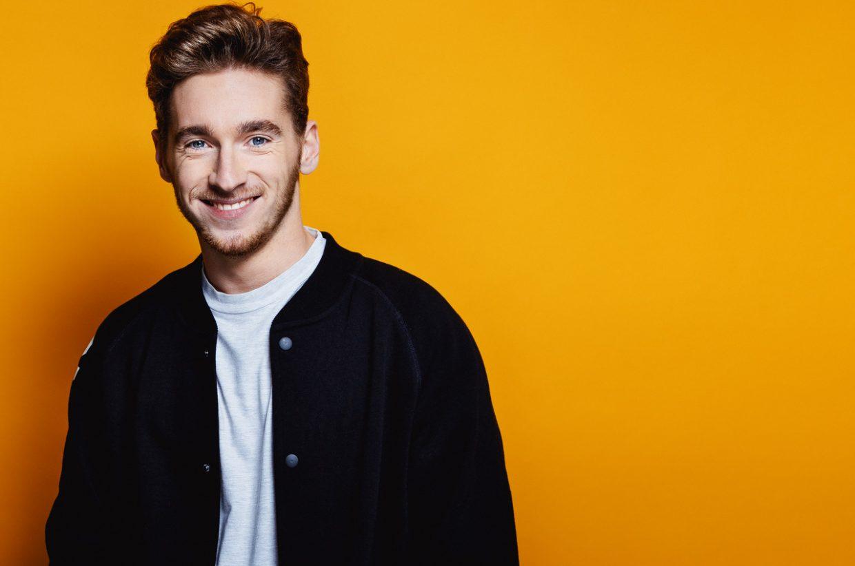 Nathan Trent posing against an orange backdrop.