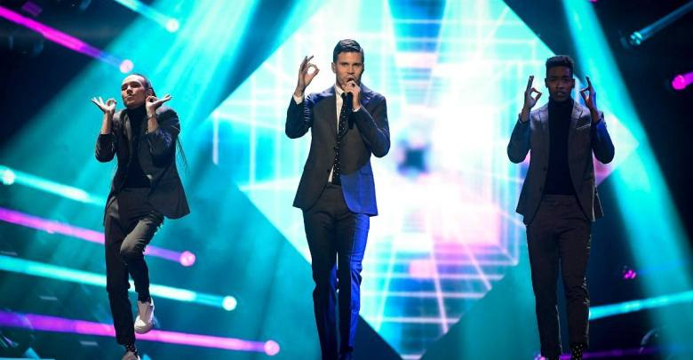 Robin Bengtsson performs on stage in a suit alongside two of his backing dancers, dancing on treadmills.