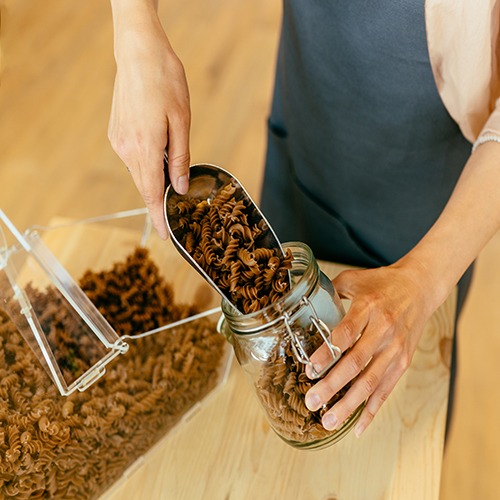 Dark brown whole grains of pasta are poured in glass jar. Close up of unrecognizable woman pouring pasta from plastic free packaging paper bag into storage jar.