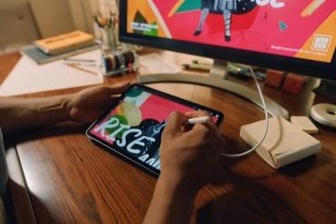 """Chico trabajando con un iPad Pro sobre una mesa y enchufado a una pantalla de ordenador. Está usando el Apple Pencil para crear algún tipo de composición publicitaria. Se lee la palabra """"RISE"""" sobre un collage en la pantalla del iPad."""