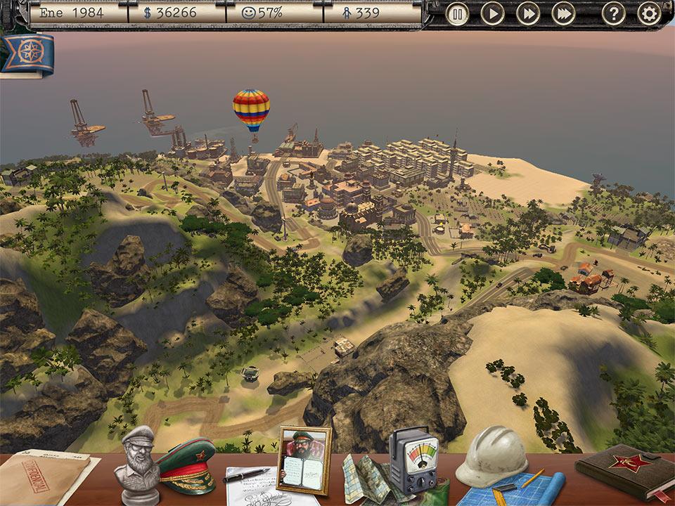 Captura de pantalla del juego Tropico. Se ve parte de una isla, con una ciudad al fondo y el mar más allá. Hay un globo aerostático volando.