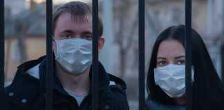 Dos personas con mascarilla tras barrotes