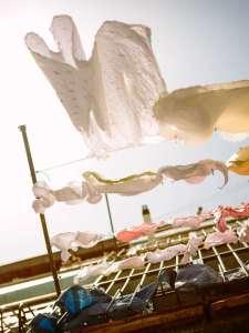 Linge étendu sur une corde entre deux facades. Entretenir tablier et torchon en lin lavé. Échoppe Végétale
