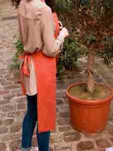 Tablier en lin lavé rouge terre cuite avec une grande poche. Tablier de cuisine et jardinage en ville. L'échoppe végétale