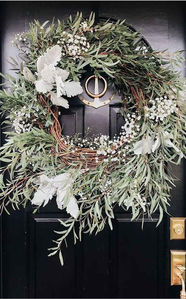 couronne de noel en eucalyptus accrochée à une porte d'entrée en bois