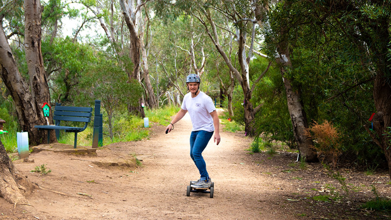 riding electric skateboard on dirt trail