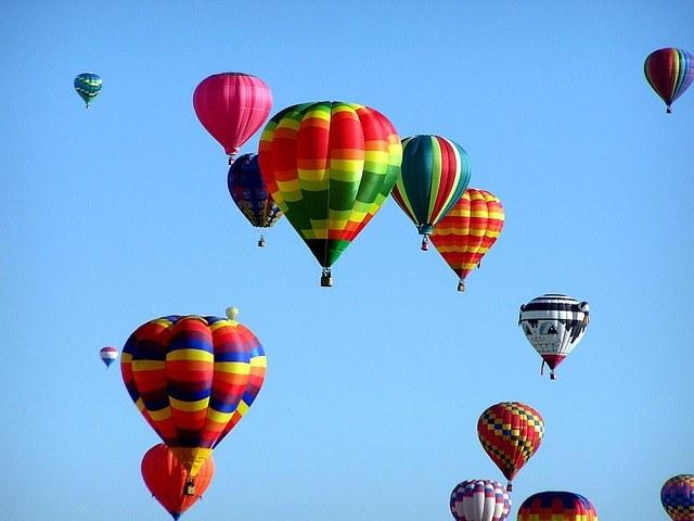large balloon rising. Blue sky.