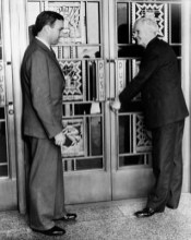 Harry Chandler opens the door on First Street lobby for his son, Norman