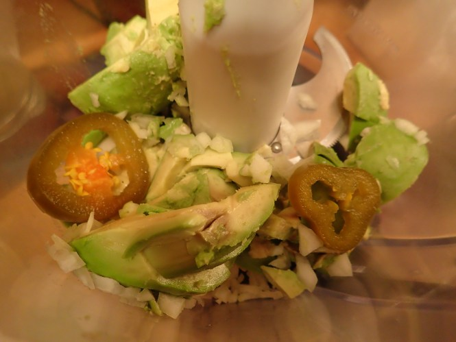 Add avocado, onions, garlic and jalapeno peppers to food processor