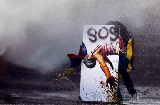 Un manifestante contra el gobierno se refugia de los cañones de agua de la policía detrás de un escudo improvisado en Caracas.