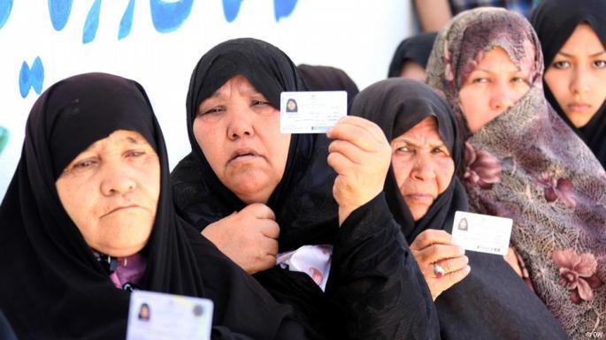 Mujeres afganas muestran sus permisos de residencia en Irán