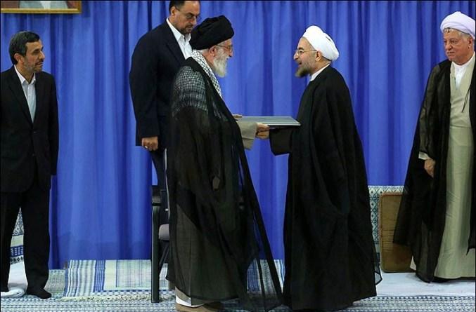 El líder supremo iraní, el ayatolá Ali Jamenei (izquierda) da una carta de apoyo a la recién elegido presidente Hassan Rohani, durante una ceremonia para su confirmación como presidente de Irán en Teherán el 03 de agosto, con el ex presidente Mahmoud Ahmadinejad a la izquierda y Hashemi Rafsanjani a la derecha.