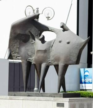 """Una representación abstracta de """"uri jeep,"""" nuestro hogar en el centro de Seúl, y el logo del """"Banco Woori,"""" nuestro banco, en la parte de atrás."""