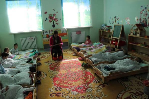 Una estudiante universitaria voluntaria lee a los estudiantes de guardería antes de la siesta en Mongolia