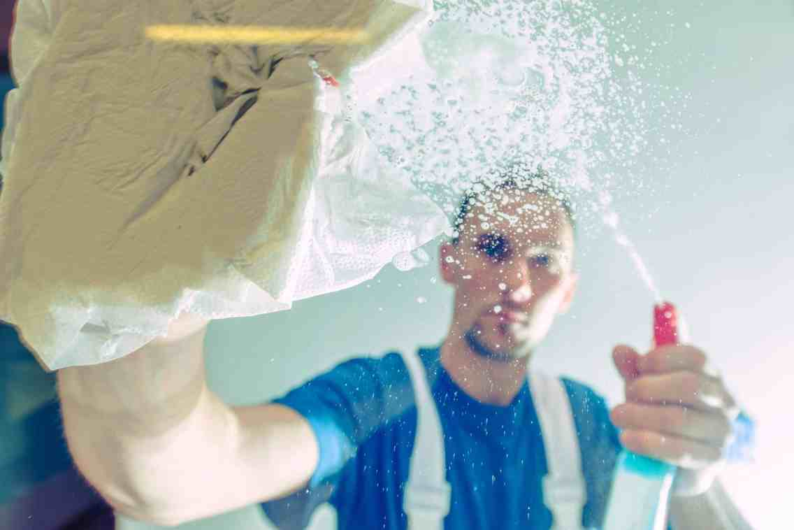 Men Cleaning Office Windows. Windows Detergent Spraying and Cleaning by Caucasian Male. Cleaning Service Worker.
