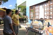 Mário explica sobre a pintura em outra parede de sua casa. Foto: Fernanda Soraggi.