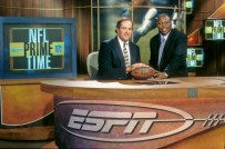 Chris Berman and Tom Jackson are shown posing with a football.