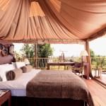 Lit d'un chambre du lodge avec vue la brousse kenyanne