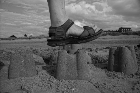 Foot hovering over sandcastle
