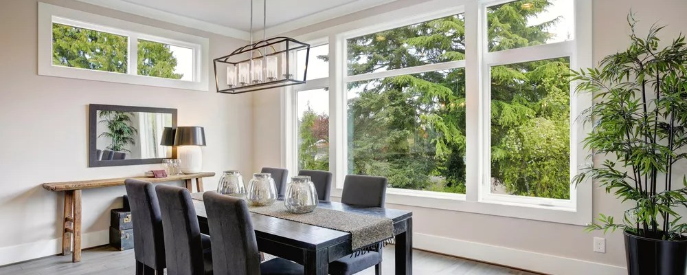 Open concept dining room with big windows and beige walls