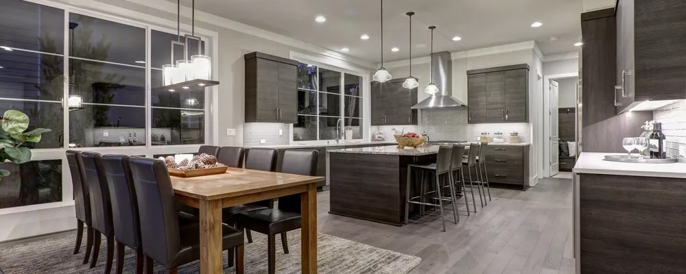 Modern open-space kitchen and dining room with lights on
