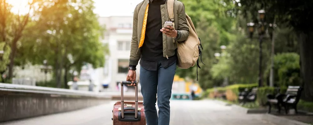 Young man walking with suitcase, looking at phone