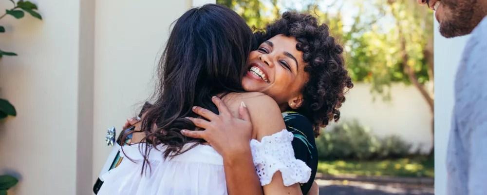 Two women hugging in doorframe
