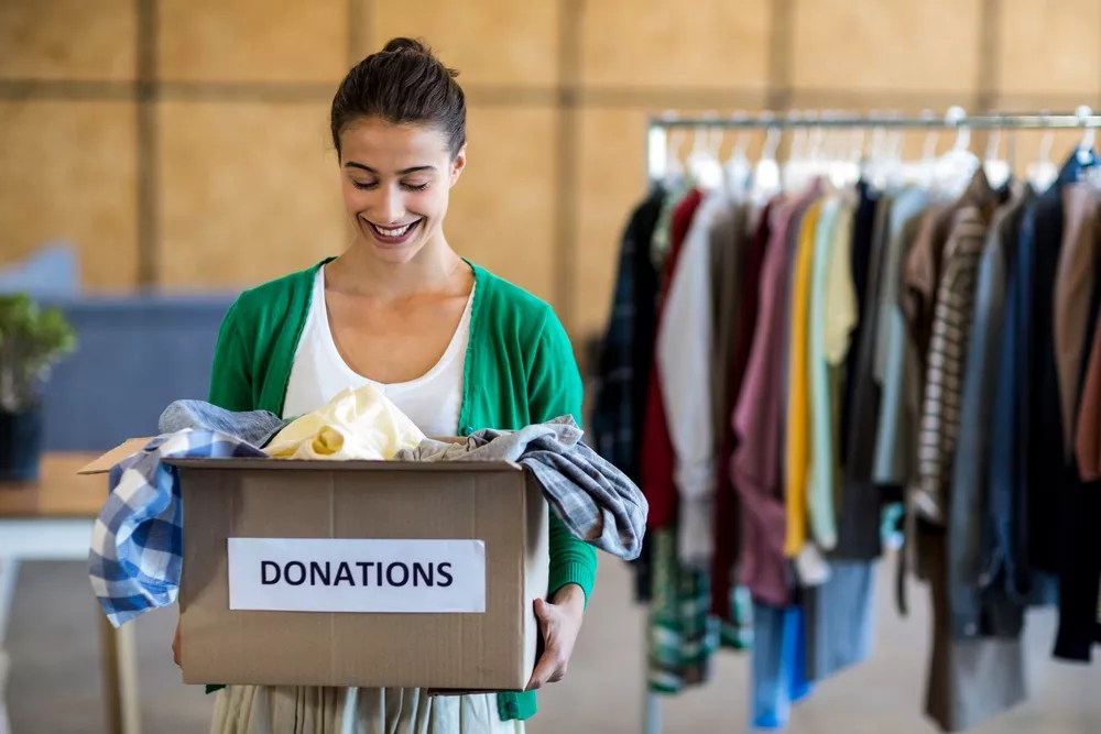 Woman carrying donations box full of clothing
