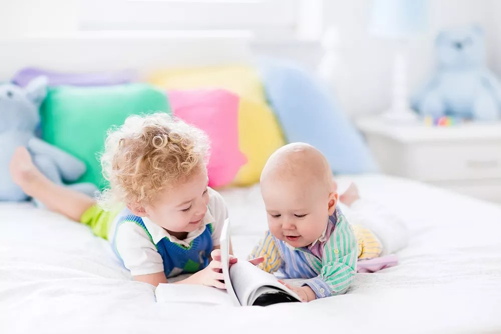 toddler reading to baby