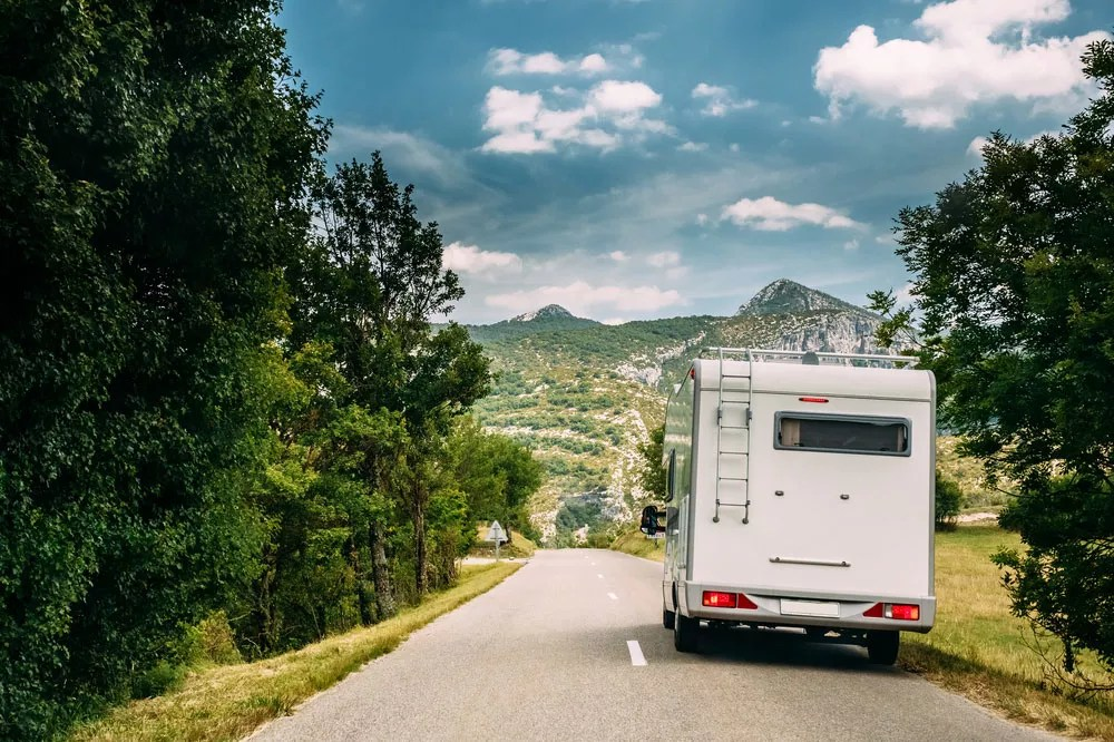 RV traveling on road in the mountains