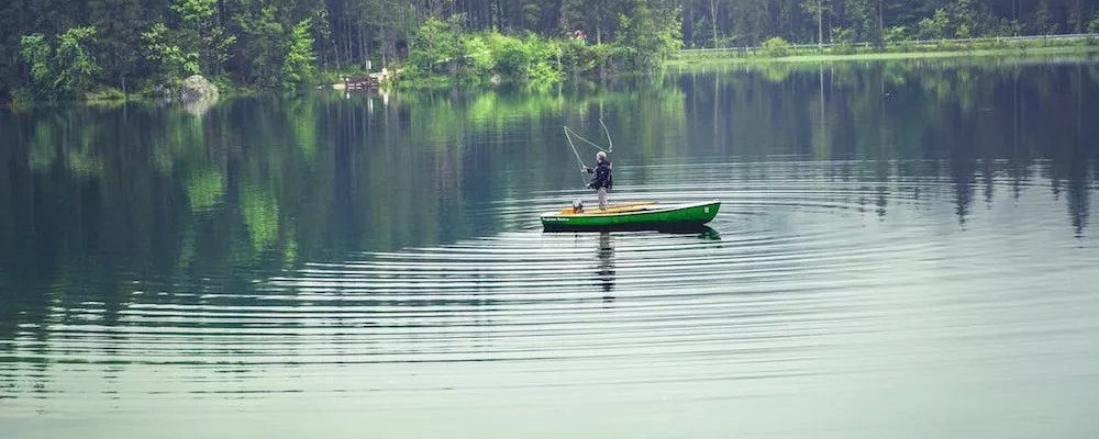 Man in fishing boat in center of lake