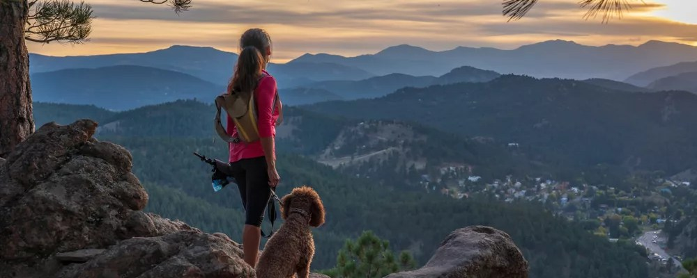 Woman standing at the top of mountain with her dog