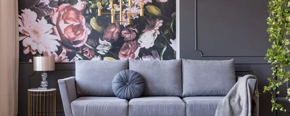 Dark gray living room with a light gray couch and pink floral accent wall