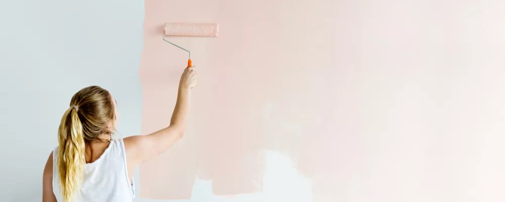 Girl painting her wall in blush pink