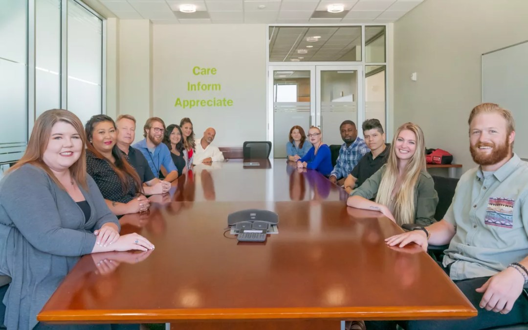 Employees at Extra Space Storage gathered around conference room table