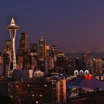 Skyline of tall buildings and Space Needle in Seattle at night.