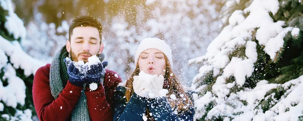 Guy and girl blowing snow.