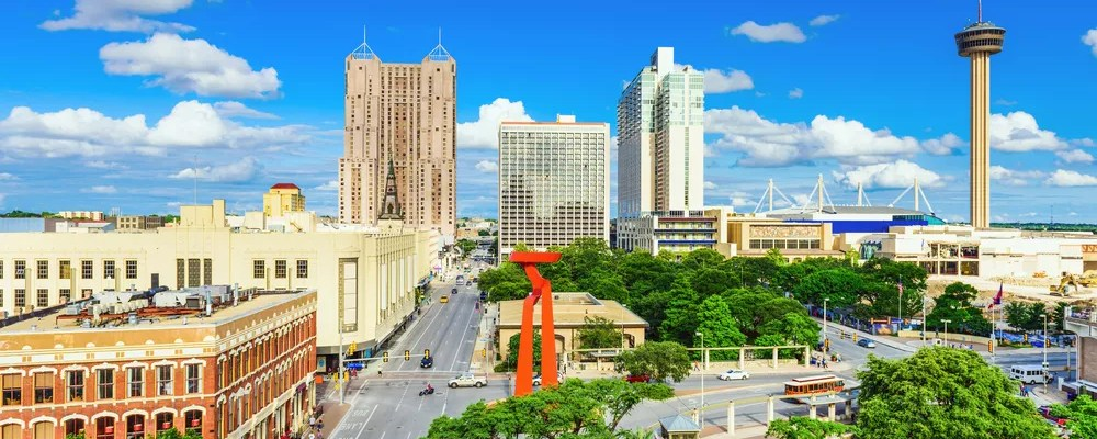 Skyline of tall buildings and green trees on sunny day in Downtown San Antonio.